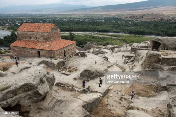 Tourists visit Uplistsikhe cave complex one of the oldest urban settlements in Georgia on August 17 2017 / AFP PHOTO / JOEL SAGET