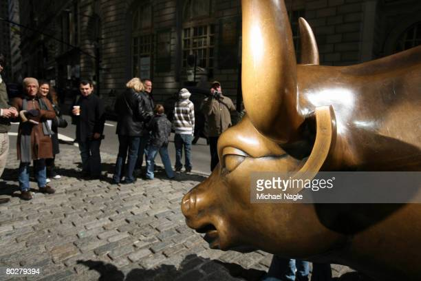 Tourists visit Wall Street's Bull March 17 2008 in New York City Stocks are volitile on Wall Street following news of JP Morgan Chase acquisition of...