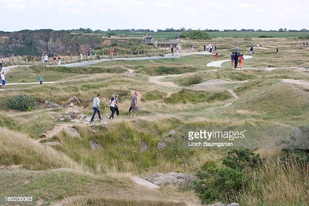 Tourists visiting destroyed German positions and the bombed area at Pointe du Hoc part of the coast during the landing of the allies in the Normandy...