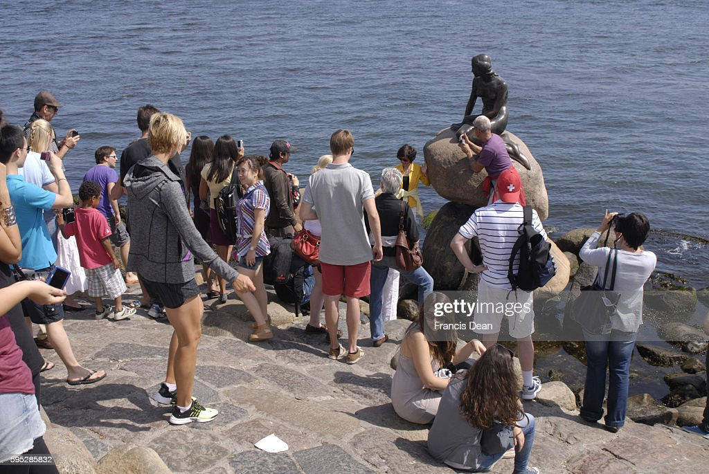 Tourists visitng little Mermaid and biy little mermaid as spuvenirs some are buy wth USA dolars bills at langeline 27 July 2011