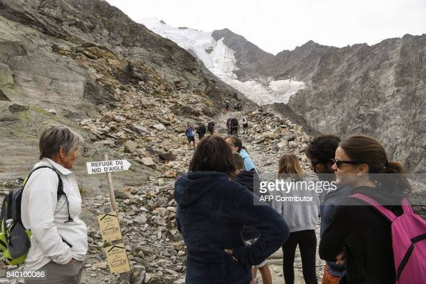Tourists wait after taking the MontBlanc Tramway at the highest station 'Le nid d'Aigle' on August 27 2017 on the MontBlanc range near SaintGervais...