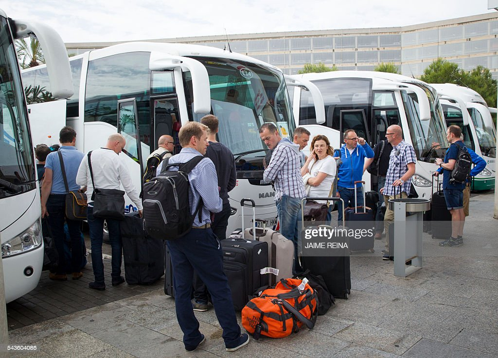 Tourists wait for buses to take them to their hotels at the Palma de Mallorca airport on June 29, 2016. As of July 1, 2016 the Balearic Island government brings launches an Ecotax, 'Ecotasa', targeting tourism businesses that will onpass the daily 0.25 Euro to two euro levy onto their clients. / AFP / JAIME