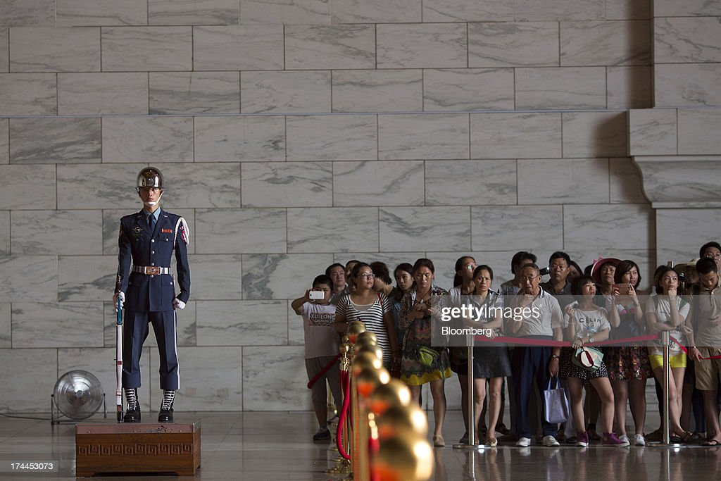 Tourists wait for the changing of the guard in the Chiang Kai Shek Memorial Hall in Taipei, Taiwan, on Wednesday, July 24, 2013. Taiwan President Ma Ying-jeou ruled out driving down the Taiwan dollar to boost exports following the currencys rally against the yen and said the government still aims for growth of at least 2 percent this year. Photographer: Jerome Favre/Bloomberg via Getty Images