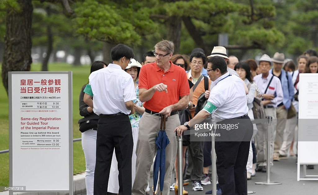 Tourists wait in line to register for a guided tour of parts of the Imperial Palace in Tokyo on June 25, 2016. The Imperial Household Agency introduced a same-day registration system for such tours to enable visitors to see the place without prior reservation.