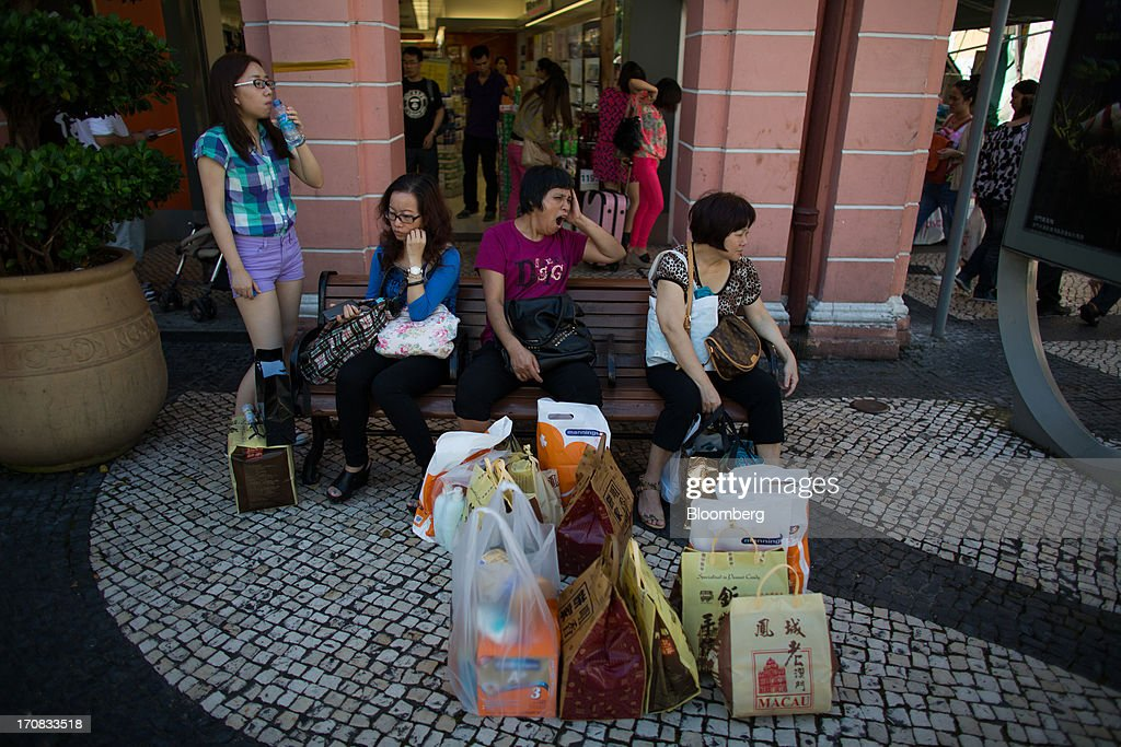 Tourists wait outside a store with shopping bags in the city center of Macau, China, on Tuesday, June 18, 2013. Casino revenue in Macau, the only place in China where casino gambling is legal, rose 14 percent to a record of 304 billion patacas ($38 billion) in 2012. Photographer: Lam Yik Fei/Bloomberg via Getty Images