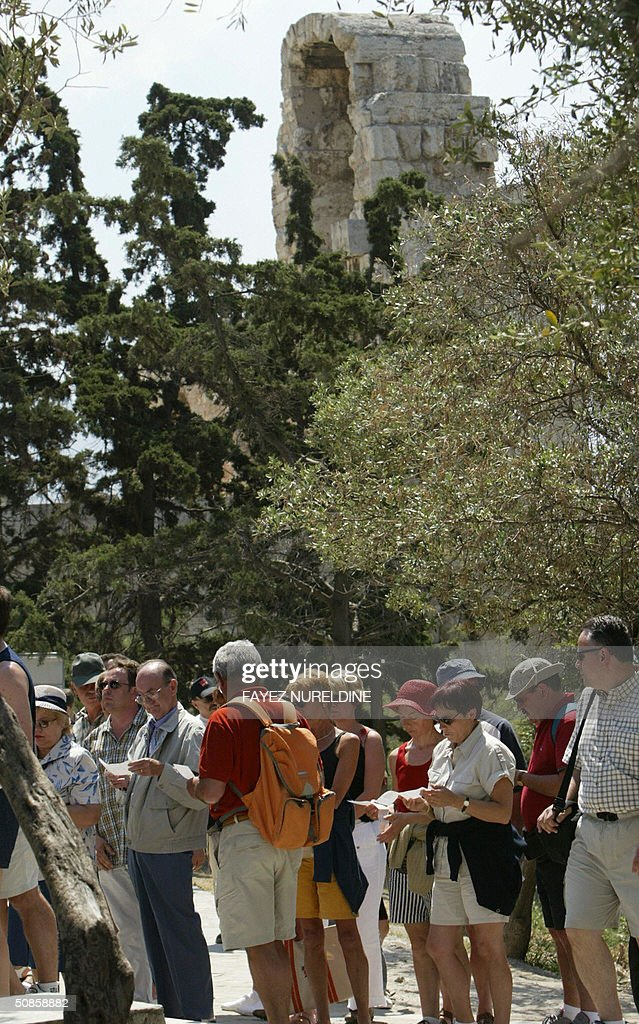 Tourists wait outside of the ancient Acropolis entrance during a demonstration of Greek Culture Ministry staff in front of the Athens Acropolis, in Athens, 20 May 2004. In demand of permanent hiring, some 200 employees on temporary work contracts blocked access to the ancient, landmark monument for around 60 minutes.