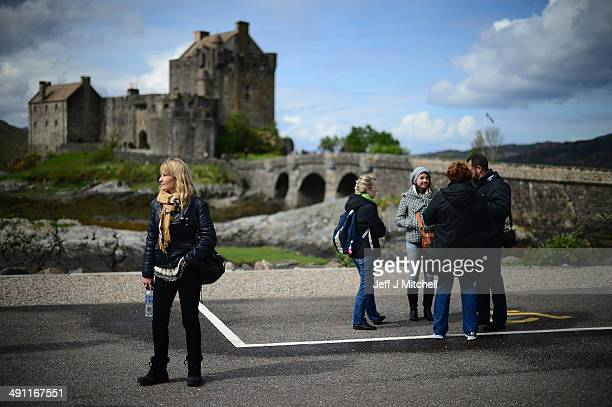 Tourists wait to board a bus next Eilean Donan Castle on May 12 2014 in Lochalsh Scotland The Isles of Harris and Lewis will vote along with the rest...