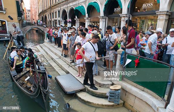Tourists wait to board a gondola on a canal in the city centre on July 21 2015 in Venice Italy With an estimated number of 27 million visitors per...
