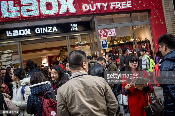 Tourists wait to enter a tax free store after getting off a tour bus in the Ginza shopping district on February 20 2015 in Tokyo Japan Tourists...