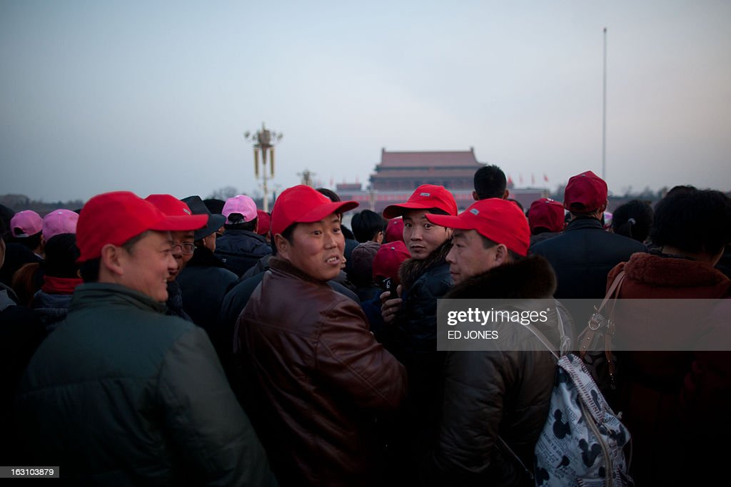 Tourists wait to watch the daily flag-raising ceremony on Tiananmen Square in Beijing early on March 5, 2013. Thousands of delegates from across China meet this week to seal a power transfer to new leaders whose first months running the Communist Party have pumped up expectations with a deluge of propaganda. AFP PHOTO / Ed Jones