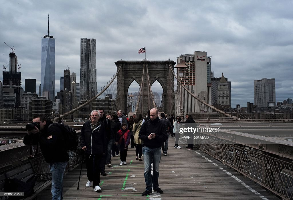 Tourists walk across the Brooklyn Bridge in New York on May 5, 2016. / AFP / Jewel SAMAD