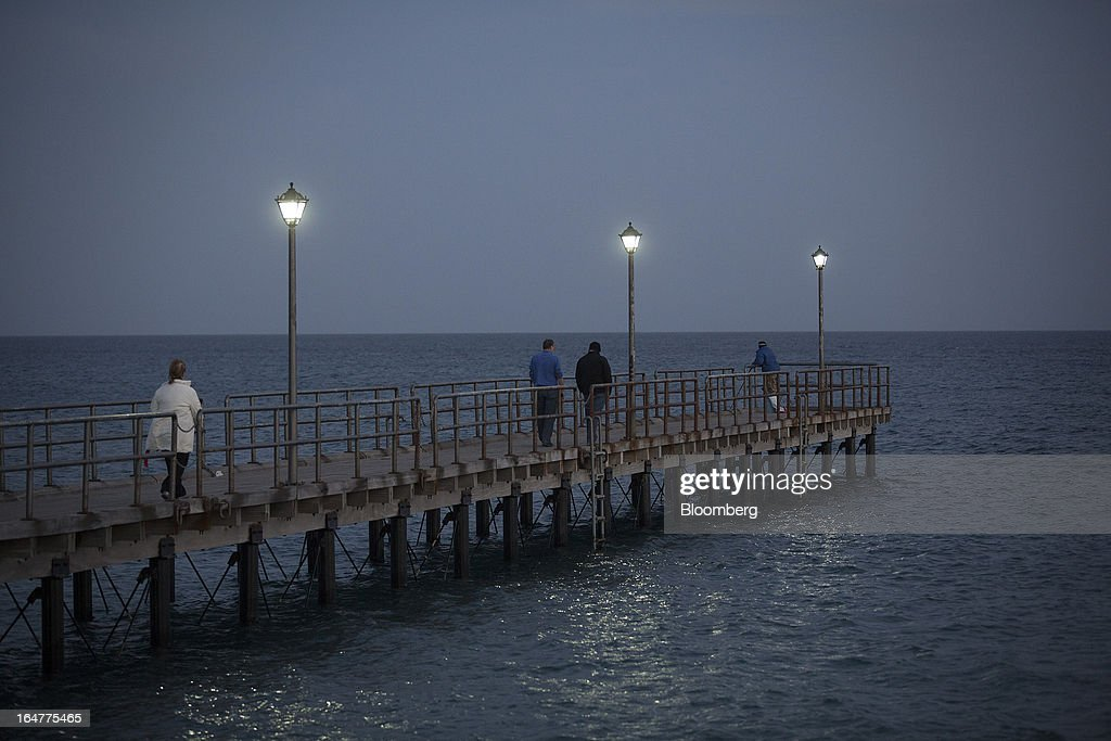Tourists walk along a pontoon illuminated by electric lights on the waterfront in Limassol, Cyprus, on Wednesday, March 27, 2013. The ECB said on March 25 it won't stop the Cypriot central bank from providing the island's banking sector with emergency funding. Photographer: Simon Dawson/Bloomberg via Getty Images