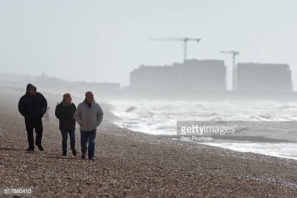 Tourists walk along Brighton Beach on March 28 2016 in Brighton England Yesterday the Met Office issued an amber warning for winds for London and...