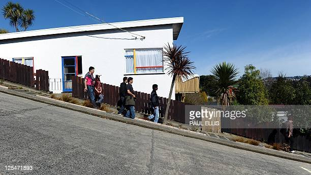Tourists walk along one of the world's steepest street in Dunedin New Zealand on September 18 2011 A race takes place up the Baldwin Street which has...
