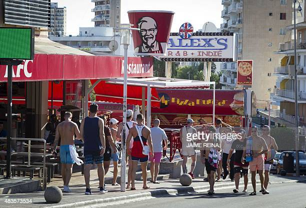 Tourists walk along Punta Ballena street in Magaluf Calvia on Mallorca Island on August 10 2015 AFP PHOTO/ JAIME REINA