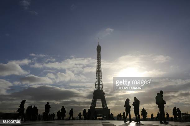 Tourists walk along the Human Right's Plaza overlooking the Eiffel Tower at sunrise in Paris on January 5 2017 / AFP / LUDOVIC MARIN