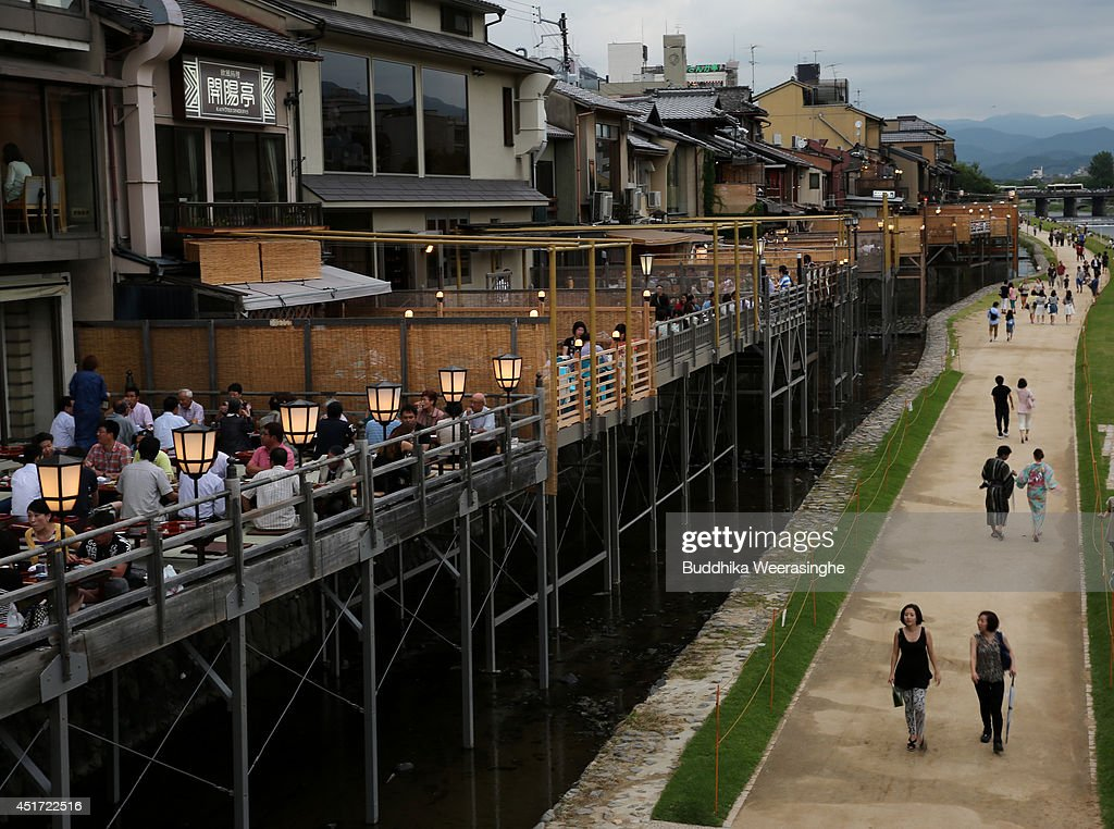 Tourists walk along the river side with outdoor restaurants at Kawaramachi on July 5, 2014 in Kyoto, Japan. Kyoto has been named the world's best city in the U.S. magazine Travel + Leisure for 2014, according to its website. The former capital of Japan is known for old temples and shrines.