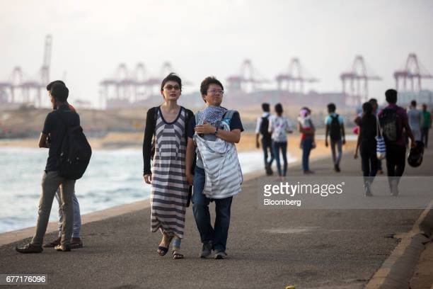 Tourists walk along the sea front of Galle Face Green as the construction site of the Colombo Port City development stands in the background in...