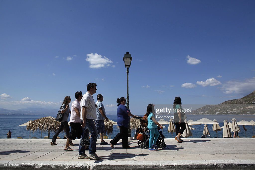 Tourists walk along the seafront past beach parasols in Loutraki, Greece, on Monday, Sept. 23, 2013. While the country's lenders are on firmer footing after getting capital from euro-area and International Monetary Fund bailout funds, they still need to reduce the non-performing loans that have tripled to 29 percent of the total in three years and threaten their new-found solvency. Photographer: Kostas Tsironis/Bloomberg via Getty Images