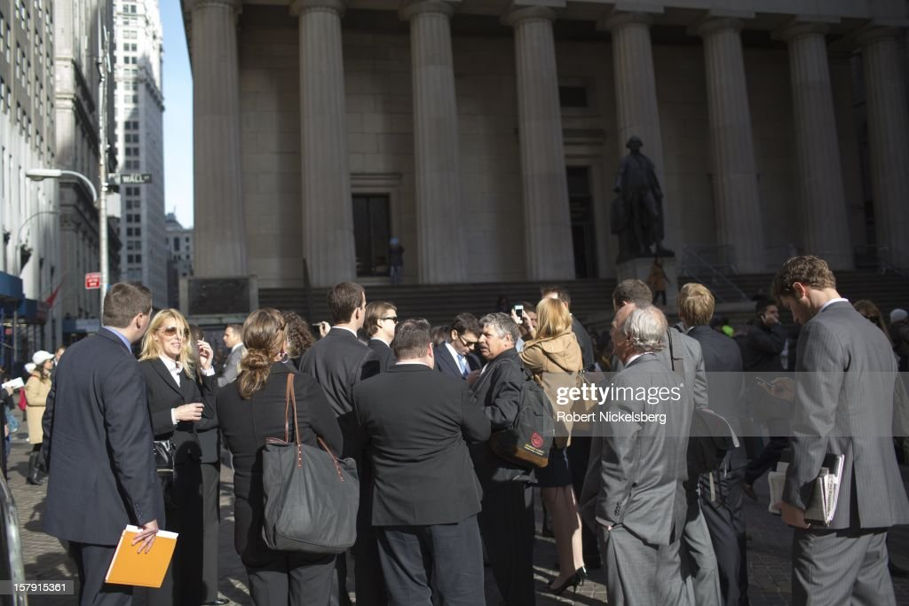 Tourists walk along Wall Street near the New York Stock Exchange and the Federal Reserve Building December 3, 2012 in the Manhattan borough of New York.