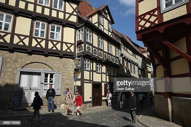 Tourists walk among halftimbered houses on April 20 2014 in Quedlinburg Germany Quedlinburg located in the Harz region dates its history to the 9th...