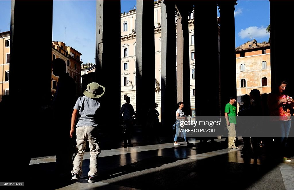 Tourists walk and stand near the colonnade of the Pantheon on June 26 , 2014 in Rome. Dating from 126 AD, the monument is the best preserved ancient building of the city.