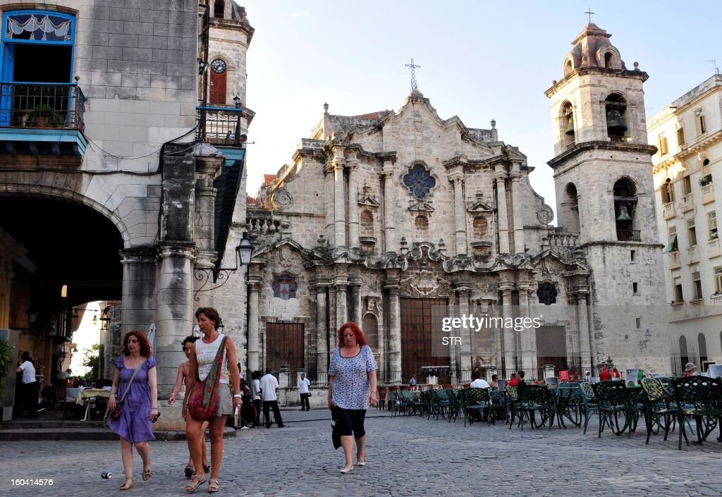 Tourists walk around Cathedral square in Old Havana, Cuba, on August 25, 2010.