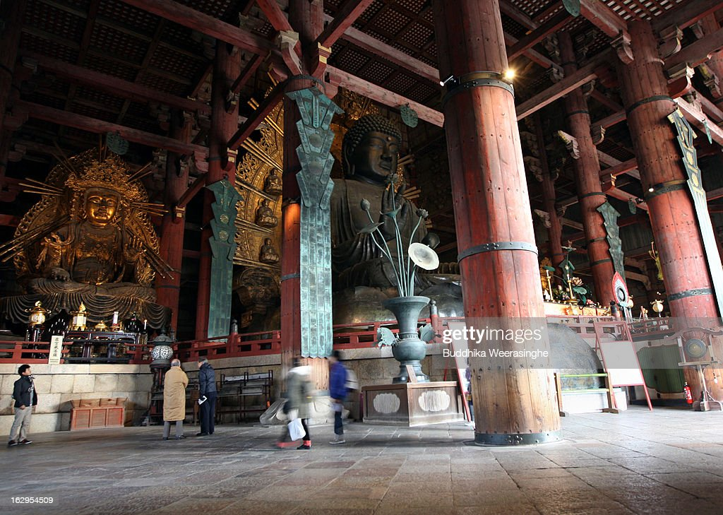 Tourists walk around the Great Buddha (R) and Bosatsu statues(L) located in the Daibutsuden (the temple's main hall) at Todaiji Temple on March 2, 2013 in Nara, Japan. The Buddhist Todaiji temple was built in 752 AD and is now one of seven sites in Nara to be listed as a UNESCO World Heritage Site.