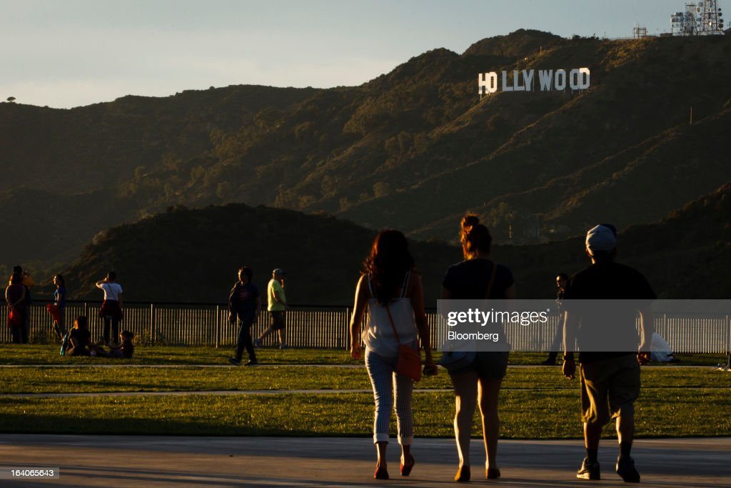 Tourists walk around the Griffith Observatory at sunset with the Hollywood Sign in the background in Los Angeles, California, U.S., on Thursday, March 14, 2013. California should start a state-run bank to finance economic development that's less polluting and more environmentally friendly, financed by auctions of greenhouse-gas carbon credits, Lieutenant Governor Gavin Newsom said. Photographer: Patrick T. Fallon/Bloomberg via Getty Images