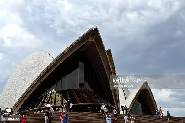 Tourists walk around the Sydney Opera House in Sydney on January 14 after it was cordoned off in a security scare sparked by 'information on social...