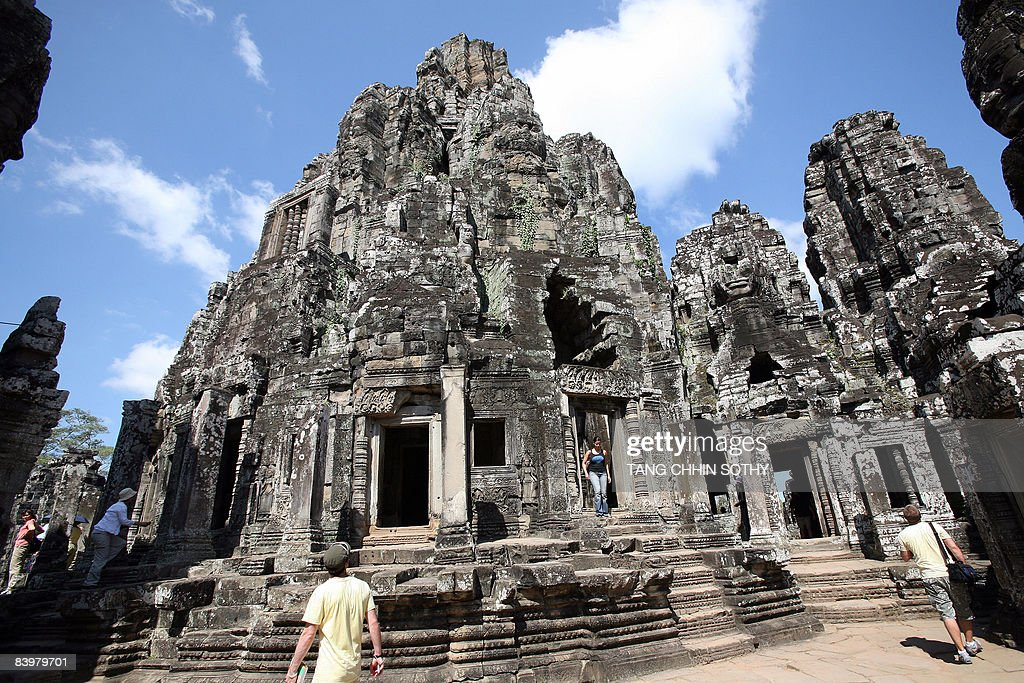 Tourists walk at Bayon temple in Siem Reap province some 314 kilometers northwest of Phnom Penh on December 7 2008 Tourist arrivals to Cambodia...