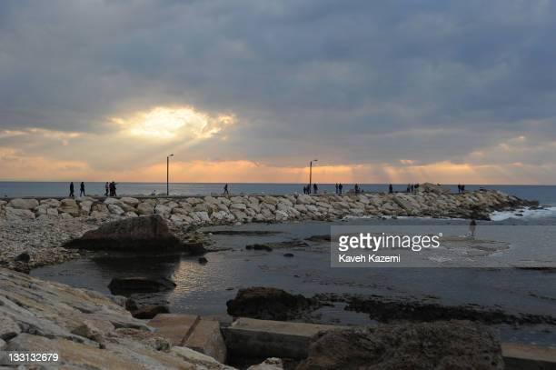 Tourists walk at sunset on Byblos pier Lebanon 2011