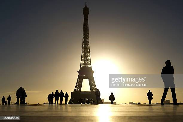 Tourists walk at the Trocadero square with the Eiffel tower in the background on December 30 2012 at sunrise in Paris AFP PHOTO LIONEL BONAVENTURE