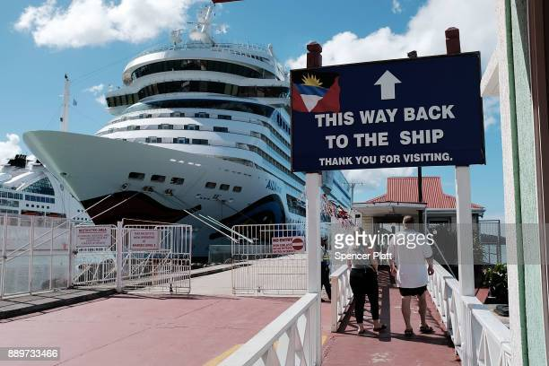 Tourists walk back to their cruise ship sitting in the harbor on December 10 2017 in St John's Antiqua While it's sister island Barbuda was nearly...