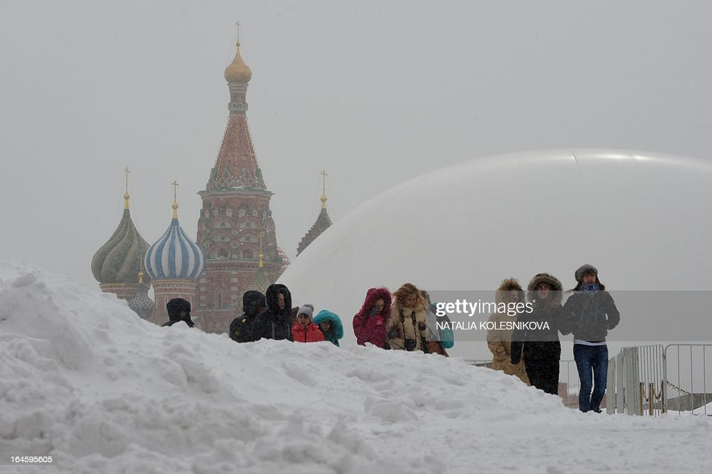 Tourists walk between snowdrifts at the Red Square in Moscow, on March 25, 2013, with a huge temporary dome covering the mausoleum of Soviet state founder Vladimir Lenin (R) rising in the background