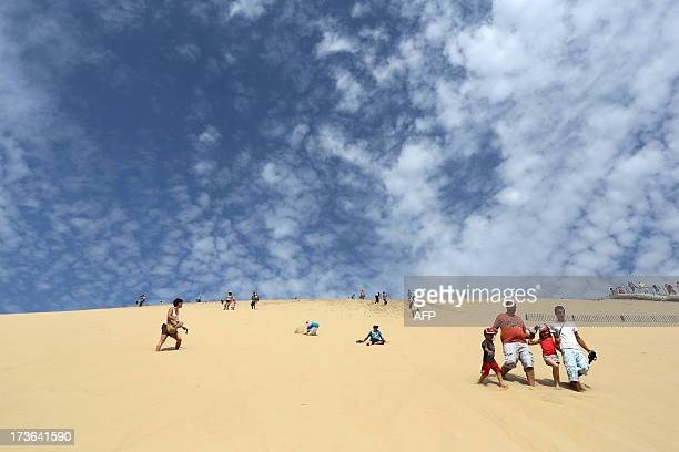 Tourists walk down from the dune of Pilat the highest sand dune in Europe on July 16 2013 at La TestedeBuch in the Arcachon bassin western France AFP...