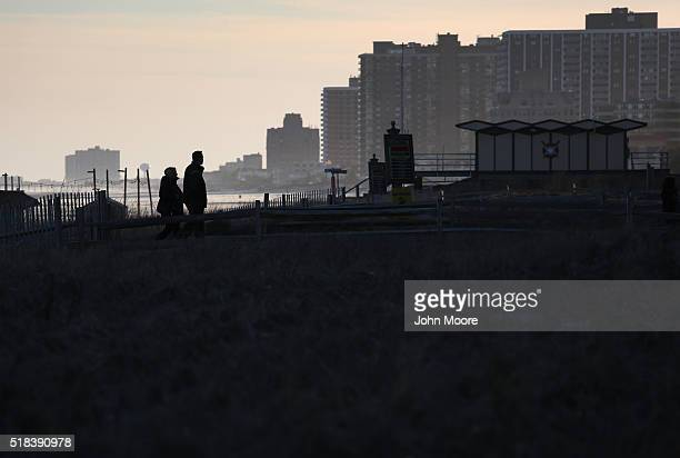 Tourists walk from the beach along the casinolined boardwalk on March 30 2016 in Atlantic City New Jersey The Atlantic City municipality is due to...