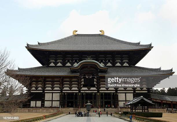 Tourists walk front of the main building of the Todaiji Temple on March 2 2013 in Nara Japan The Buddhist Todaiji Temple was built in 752 AD and is...