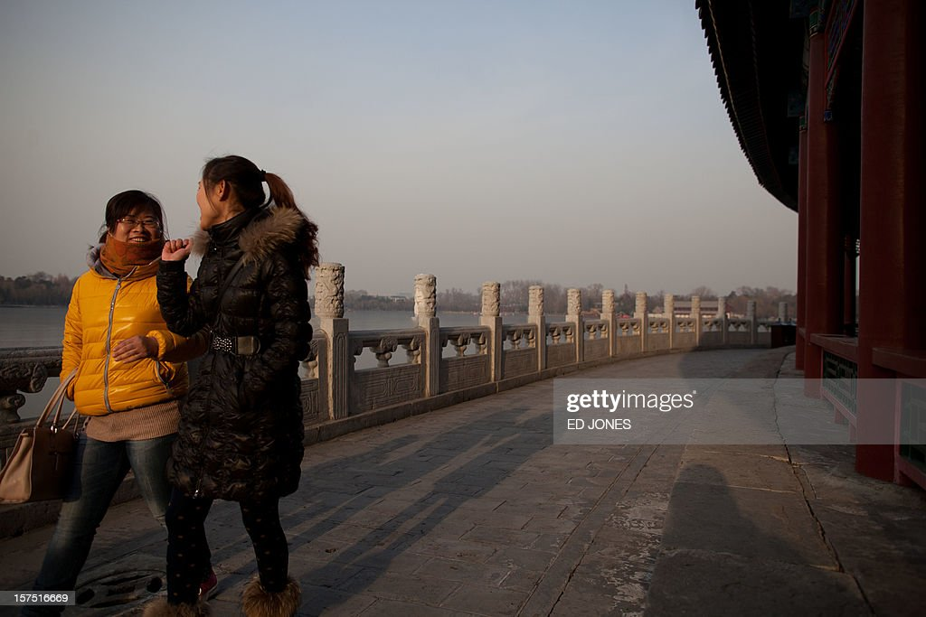Tourists walk in Beihai park in Beijing on December 4, 2012. The latest batch of purchasing managers' indexes from HSBC show manufacturing activity in China hit a 13-month high, while India also saw its strongest expansion since June. AFP PHOTO / Ed Jones