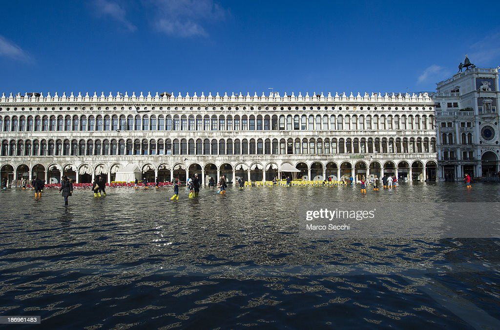 Tourists walk in front of the Procuratie Vecchie in Saint Mark's Square during today's Acqua Alta on November 5, 2013 in Venice, Italy. The high tide, or acqua alta as it is locally known, is a natural event most commonly affecting the city during Autumn and Winter.