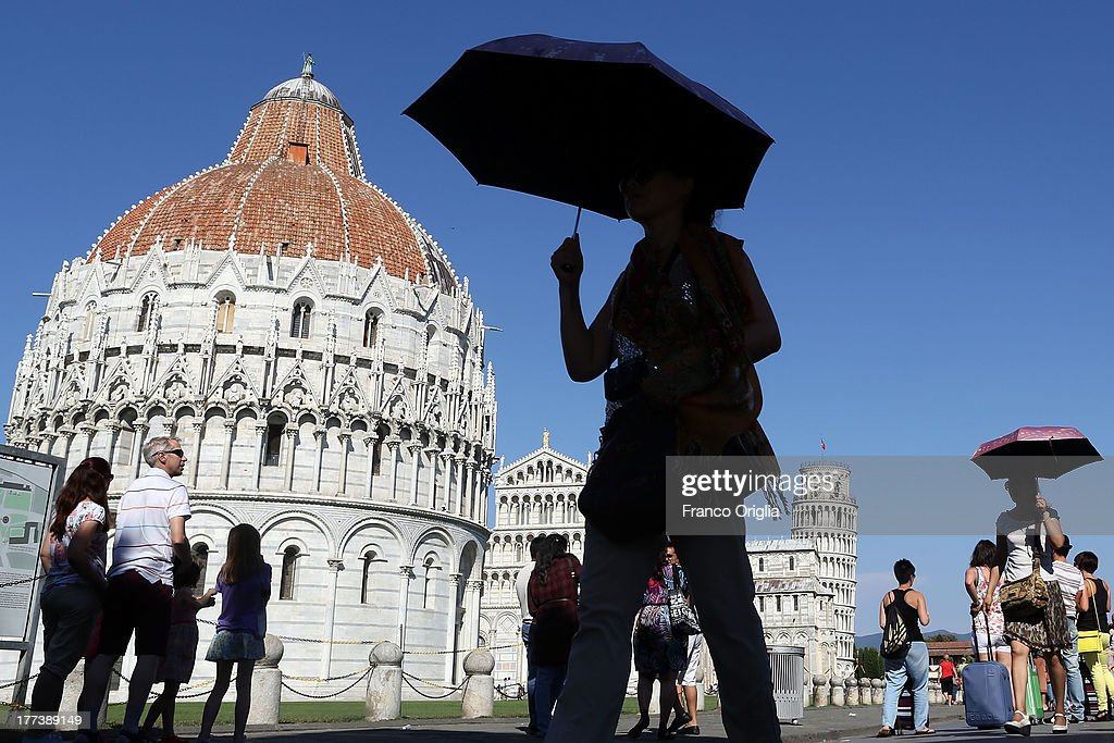 Tourists walk in Piazza dei Miracoli, Square of Miracles, in front of the Leaning Tower of Pisa, Torre pendente di Pisa, on August 10, 2013 in Pisa, Italy.