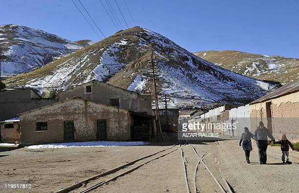 Tourists walk in Pulacayo a former mining center near the Uyuni salt flat in the Potosi department Bolivia on July 20 2011 The Uyuni salt flat has an...