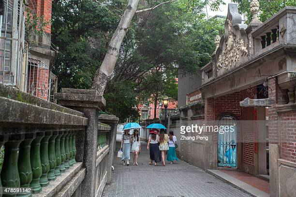 Tourists walk in the alley between historical buildings Kulangsu is an island off the coast of Amoy city After the First Opium War Amoy became a...