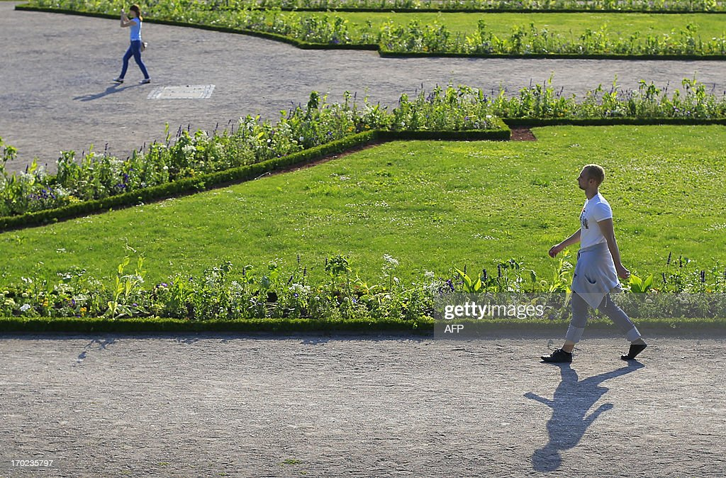 Tourists walk in the garden of the Belvedere Palace in Vienna on June 9, 2013. Meteorologists forecast temperatures around 25 degrees for central Austria. AFP PHOTO / ALEXANDER KLEIN