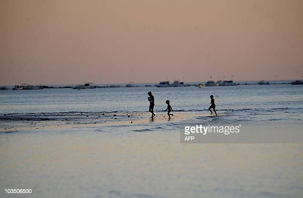 Tourists walk in the sea on the Sanlucar de Barrameda's beach in southern Spain on August 20 2010 AFP PHOTO/ CRISTINA QUICLER