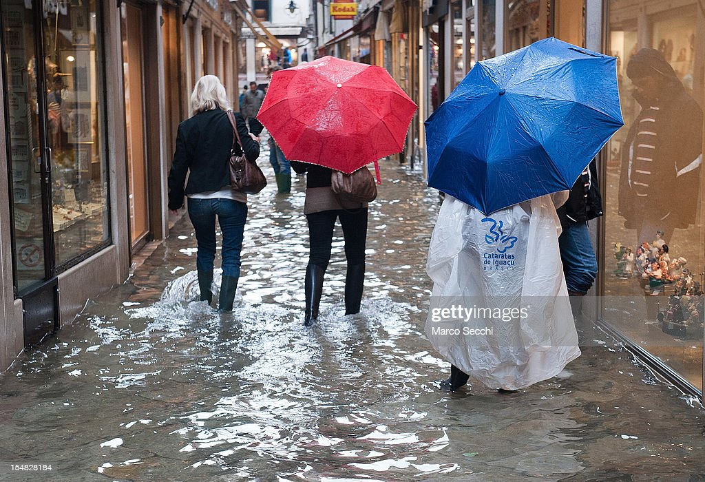 Tourists walk in the water near Rialto Bridge during a high tide on October 27, 2012 in Venice, Italy. The high tide, or acqua alta as it is locally known, stood at 127 centimeters this morning.