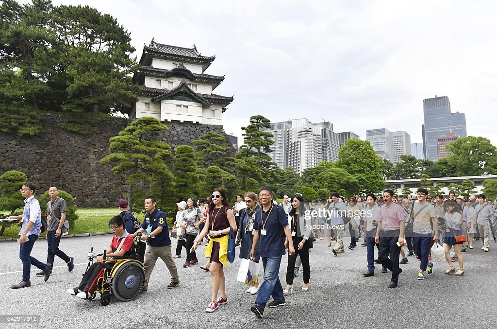 Tourists walk inside the Imperial Palace in central Tokyo on June 25, 2016. The Imperial Household Agency introduced a same-day registration system for guided tours of parts of the imperial grounds to enable visitors to see the place without prior reservation.