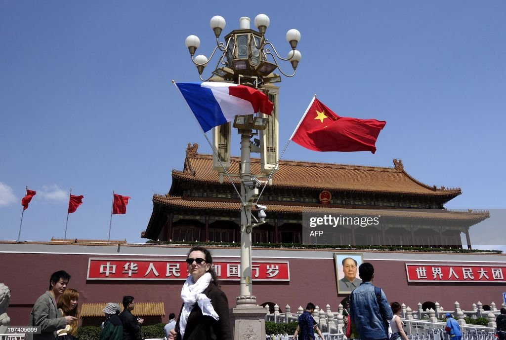 Tourists walk near a French (L) and Chinese national flag (R) at Tiananmen square in Beijing on April 25, 2013. French President Francois Hollande arrived in Beijing on April 25 on a trip aimed at boosting exports to China, with hopes that deals can be reached over the sale of aircraft and nuclear power.
