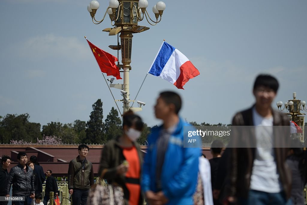 Tourists walk near a French (R) and Chinese national flag (L) at Tiananmen square in Beijing on April 25, 2013. French President Francois Hollande arrived in Beijing on April 25 on a trip aimed at boosting exports to China, with hopes that deals can be reached over the sale of aircraft and nuclear power.
