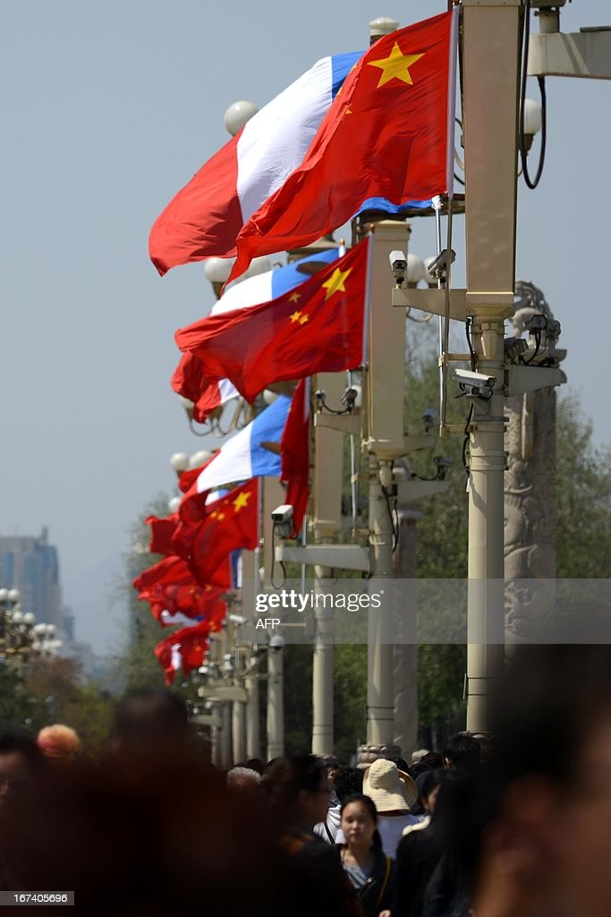 Tourists walk near French (L) and Chinese national flags (R) at Tiananmen square in Beijing on April 25, 2013. French President Francois Hollande arrived in Beijing on April 25 on a trip aimed at boosting exports to China, with hopes that deals can be reached over the sale of aircraft and nuclear power.